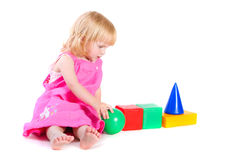 Baby in pink dress playing with bright blocks. Studio shot stock photography