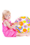 Baby in pink dress playing with colorful ball. On white background royalty free stock photography