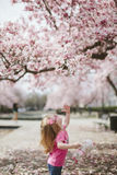 Baby in Pink Dress Trying to Reach Pink Flower Royalty Free Stock Photography