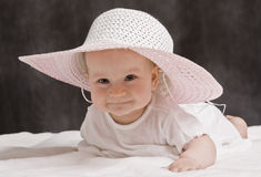 Baby with pink hat. And white dress lying Stock Image