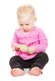Baby in pink jacket and black trousers consider Stock Images