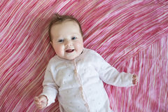 Baby on pink sheet. Adorable baby on pink sheet Royalty Free Stock Images