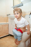 Baby pissing on   toilet Stock Image