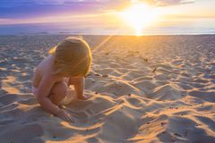 Baby plaing in sand on the coast of Baltic sea during sunset royalty free stock photography