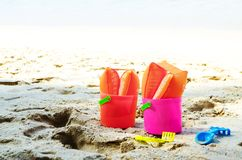 Baby plastic bucket with toys on sandy seaside Royalty Free Stock Photo