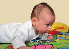 Baby play. Infant laying on his stomach on a colourful mat lifting his head Stock Photos