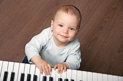 Baby play black and white piano. Portrait of little baby child play music on black and white piano keyboard stock images