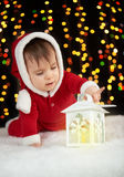 Baby play with candle lantern in christmas decoration, dressed as Santa, boke lights on dark background, winter holiday concept Stock Image
