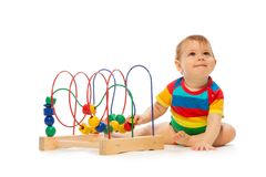 Baby play with developing toys. Little happy toddler playing with developing toy puzzle sitting isolated on white Royalty Free Stock Photography