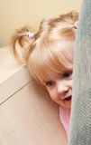 Baby play hide and seek. Cute baby girl play hide and seek at home, hiding behind sofa Royalty Free Stock Image
