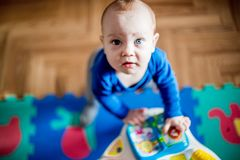 Cute boy play standing. Baby play in his room, cute male baby boy, 8 month old Stock Photos
