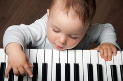 Baby play music on piano keyboard. Portrait of little baby child play music on black and white piano keyboard royalty free stock images