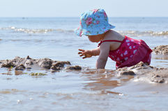 Baby play with sand. Infant child on a beach play in water Royalty Free Stock Photography