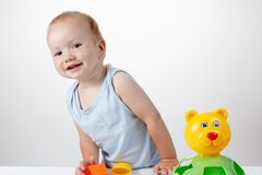 Baby play with toy in blue dress smiling Royalty Free Stock Image