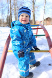 Baby on playground outdoors in winter Royalty Free Stock Image