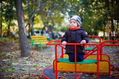 Baby on the playground. Baby plays on the playground alone in autumn Royalty Free Stock Photos