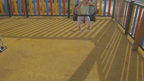 Baby in playground. Smiling baby girl in panama hat having fun riding a chain swing. Baby in playground. Smiling baby girl in panama hat having fun riding a stock video footage