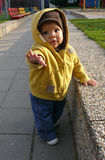 Baby on playground standing. Baby boy on playground reaching out his hand to help him walk Stock Photo