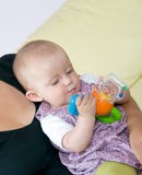 Baby playing. With toy. Baby is sitting on mother's lap stock photo