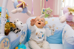 Baby playing. Six month baby playing with toys in bed. Baby tries to catch flying toy Stock Photos