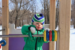 Baby playing with abacus. In outdoor playground in winter Stock Image
