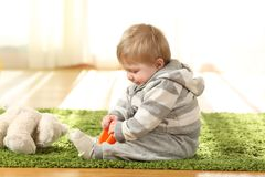 Baby playing alone with toys. On a carpet on the floor at home stock photo