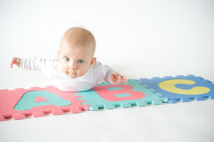 Baby playing alphabet puzzle Stock Photo