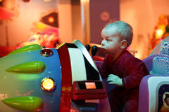Baby playing arcade game machine. At an amusement park Royalty Free Stock Images