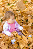 Baby playing with autumn leaves Royalty Free Stock Photo