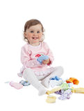 Baby playing with baby clothes, isolated on white background. Baby playing in studio on white background. Charming baby in rose dress playing with baby clothes stock images