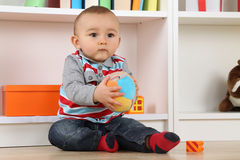 Baby playing with ball. Portrait of a baby playing with a ball in children's room Royalty Free Stock Images