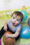 Baby playing with balloons Stock Images