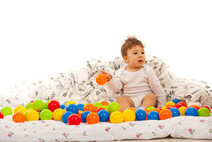 Baby playing with balls in bed Stock Photos
