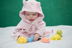 Baby playing with bathrobe. 6 months baby girl playing with pool toys wearing a bathrobe royalty free stock photography