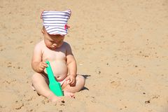Baby playing on the beach stock images