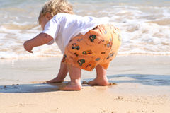 Baby playing on beach. A back view of an adorable child, bending to touch the sand on a beach royalty free stock photography