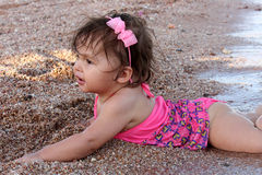 Baby playing on the beach Stock Image
