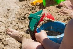 Baby playing with beach bucket and shovel. stock photos