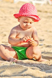 Baby playing on the beach Stock Photos