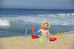 Baby playing with beach toys in the sand. Summer vacation: Baby playing with beach toys in the sand Royalty Free Stock Photo