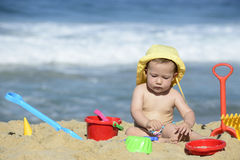 Baby playing with beach toys in the sand Stock Photography