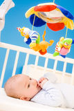 Baby playing in bed. Four months old baby resting on crig at nursery and plying with his little thumb. Toys are officially property released royalty free stock photos