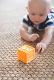 Baby Playing with Block on Woven Rug Royalty Free Stock Photography