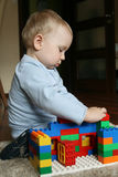 Baby playing with blocks. 17 months old baby boy playing with plastic blocks in room on the carpet royalty free stock photography