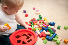 Baby playing with blocks and sorting shapes. At home royalty free stock image