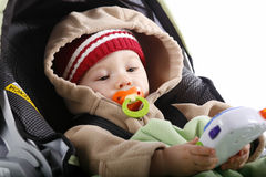 Baby playing in car seat. Cute baby in warm clothing entertaining himself with a game Stock Images