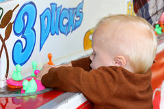 Baby Playing Carnival Duck Game. A cute baby boy is grabbing a handful of ducks as they float by during a summer carnival duck game Stock Photos
