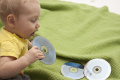 Baby is playing with cd stock photos