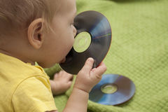 Baby is playing with cd stock photo