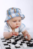 Baby playing checkers on white Royalty Free Stock Image